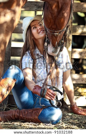Young cowgirl with horse kissing her