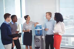 Young coworkers discussing while standing at office