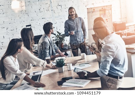 Young coworkers. Top view of modern young man conducting a business presentation while standing behind the glass wall in the board room #1094451179