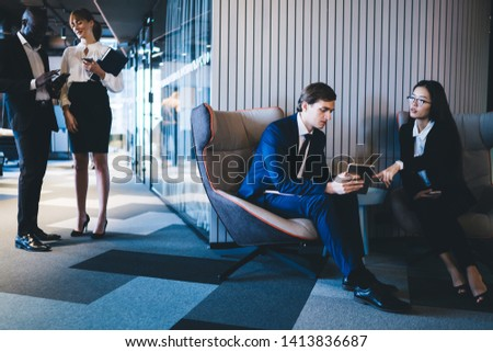 Young coworkers with tablet sitting in armchairs in hallway with multiracial colleagues standing near communicating and coworking in modern office  #1413836687