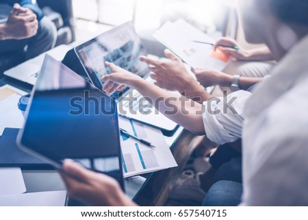 Young coworkers working on laptop computer at office.Woman holding tablet hand and pointing on touch screen. Horizontal, blurred background.Cropped