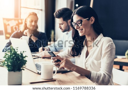 Young coworkers. Young modern colleagues in smart casual wear working while spending time in the office #1169788336