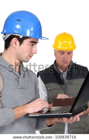 young craftsman working on his laptop while senior craftsman is taking notes - stock photo