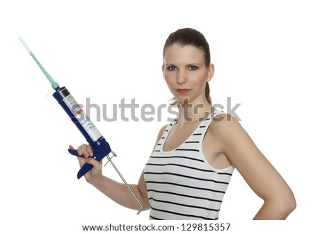 Young craftswoman with a caulking gun in front of white background