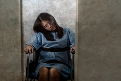 young crazy and mentally insane Asian woman restrained in wheelchair at mental hospital suffering psychiatric disorder as schizophrenia looking catatonic in Korean horror movie style