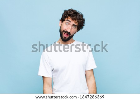 young crazy bearded man feeling puzzled and confused, with a dumb, stunned expression looking at something unexpected against flat wall