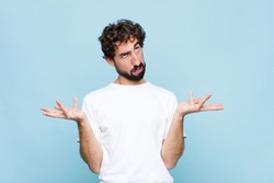 young crazy bearded man shrugging with a dumb, crazy, confused, puzzled expression, feeling annoyed and clueless against flat wall