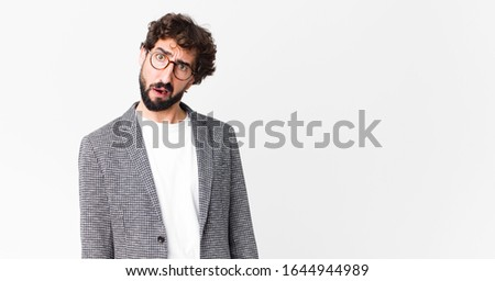 young crazy businessman feeling puzzled and confused, with a dumb, stunned expression looking at something unexpected against flat wall
