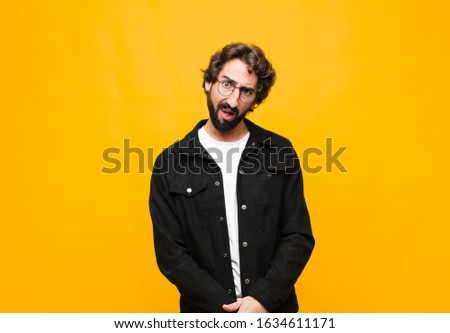 young crazy handsome man feeling puzzled and confused, with a dumb, stunned expression looking at something unexpected against orange wall