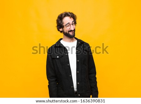 young crazy handsome man looking happy and friendly, smiling and winking an eye at you with a positive attitude against orange wall Stock fotó ©