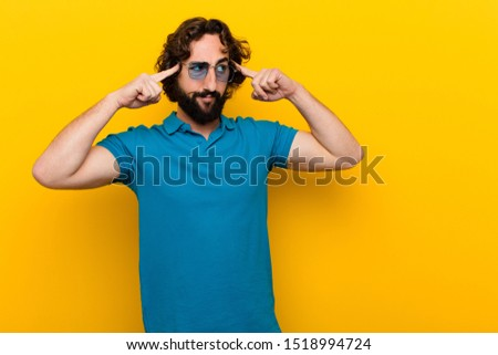 young crazy man feeling confused or doubting, concentrating on an idea, thinking hard, looking to copy space on side against orange wall