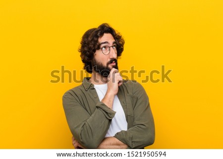 young crazy man feeling thoughtful, wondering or imagining ideas, daydreaming and looking up to copy space against yellow wall #1521950594