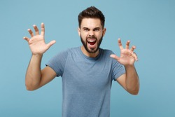 Young crazy man in casual clothes posing isolated on blue background in studio. People sincere emotions lifestyle concept. Mock up copy space. Shouting, growling like animal, making cat claws gesture