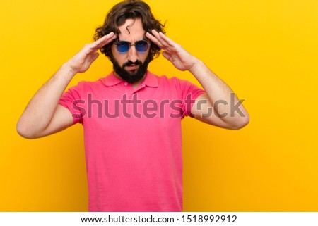young crazy man looking concentrated, thoughtful and inspired, brainstorming and imagining with hands on forehead against orange wall #1518992912