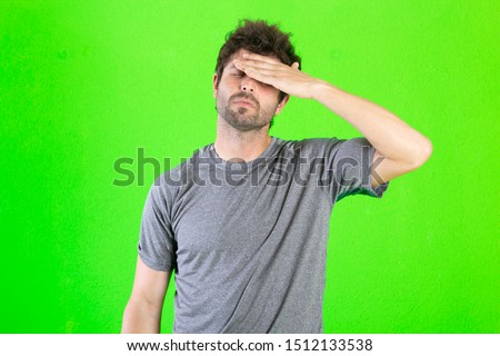 young crazy man looking stressed and frustrated on green background Foto stock ©