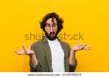 young crazy man shrugging with a dumb, crazy, confused, puzzled expression, feeling annoyed and clueless against yellow wall Stock foto ©