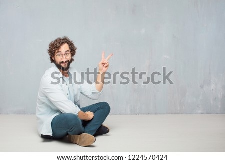 young crazy man sitting. with a proud, happy and confident expression; smiling and showing off success while gesturing victory, giving an
