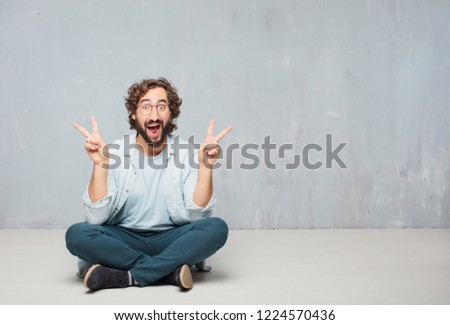 young crazy man sitting. with a proud, happy and confident expression; smiling and showing off success while gesturing victory with both hands, giving an