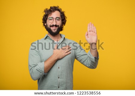 young crazy man smiling confidently while making a sincere promise or oath, solemnly swearing with one hand over heart.