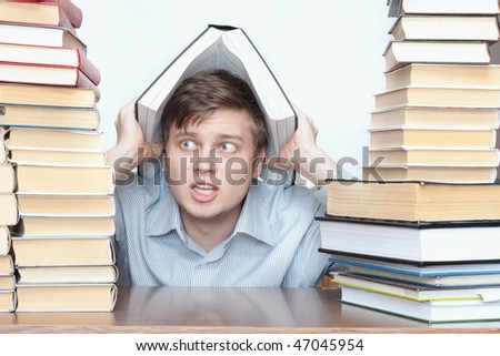 Young crazy student hold big book over head between books