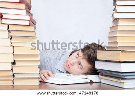 Young crazy tired discontent student between books
