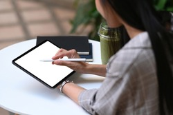 Young creative designer holding stylus pen drawing on screen of digital tablet while sitting at the park.