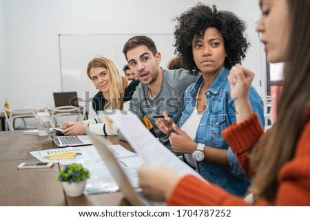 Young creative designers working in a project and discussing new order development on workplace. Business and team work concept. Stockfoto ©