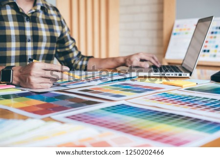 Young creative Graphic designer using graphics tablet to choosing Color swatch samples chart for selection coloring with work tools and accessories at workplace. #1250202466