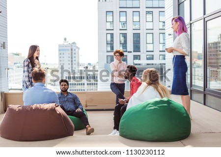 Young creative multiethnic people gesturing and discussing something with coworkers while sitting at the office lounge zone on soft poufs #1130230112