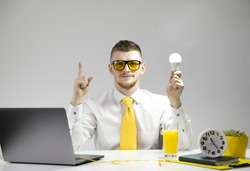 Young creative office specialist in white shirt, yellow tie, glasses with shining lamp (light bulb) in hand pointing upward. Successful business startup, innovation, genius idea, new project concept