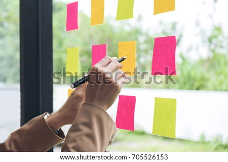 Young creative professional leader using post it notes in glass wall to writing strategy business plan, management and people concept. #705526153