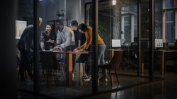 Young Creative Team Meeting with Business Partners in Conference Room Behind Glass Walls in Agency. Colleagues Sit Behind Conference Table and Discuss Business Opportunities, Growth and Development.