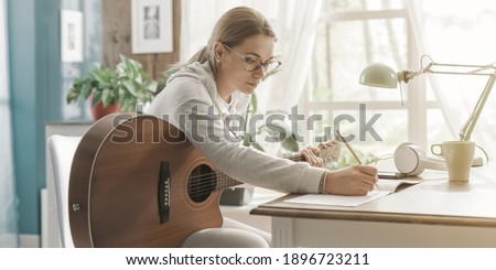 Young creative woman playing guitar at home and composing music Foto stock ©