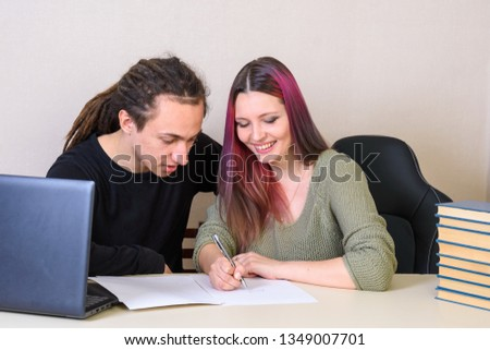 Young creative young man and girl at the table writing on paper