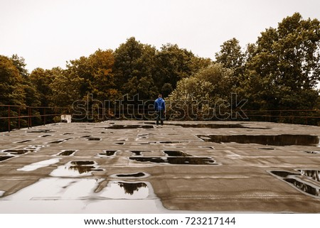 Young criminal guy standing on the roof top of old hotel in forest in autumn. (Urbex) Man hooligan sneaked to the old hotel balcony with water. Faceless man in hood on  rooftop with forest background