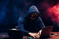 young criminal male hides his face under the hood and mask, hacks the password on the laptop, typing something. anonymous, incognito guy going to hack. cyberattack concept