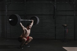 Young cross fit athlete lifting barbell overhead at the gym. Copy space