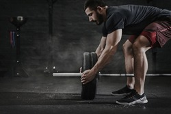 Young cross fit athlete preparing barbell for lifting weight at the gym. Magnesia protection dust cloud. Handsome man doing functional training. Practicing powerlifting. Workout exercises.