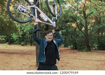 Young cuacasian man crashes the bicycle hodlig it up in the hands, angry expression on the face. Outdoors, autumn/fall park, golden leaves. Strong emotions, funny/humor pic. Hate bicycle, hating sport