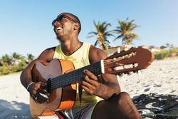Young cuban man having fun in the beach with his guitar. Friendship concept.