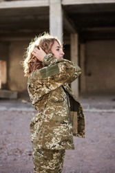 Young curly blond military woman, wearing ukrainian army military uniform and black t-shirt. Three-quarter portrait of female soldier in rim light glare in front of ruined abandoned building.