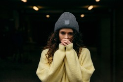 Young curly  girl in yellow sweater and gray cap stay alone at the city lights and freeze