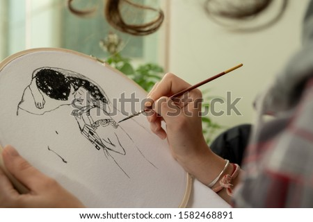 Young curly lady paints on the t-shirt with textile colors on a wooden frame, wearing the plaid shirt on the terrace