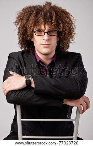 young curly man in suit sit on chair wearing eyeglasses, studio shot