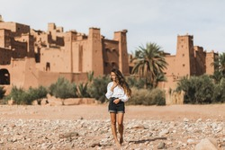 Young curly woman eastern appearance walking on background of kasbah Ait-Ben-Haddou. Travel in Morocco, Ouarzazate. Summer vacations, travel lifestyle concept.
