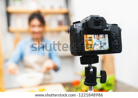 Young cute Asian blogger girl recording video tutorial session of salad cooking lesson at home kitchen. Food blogging or vlogging, social media hobby broadcasting, or online learning course concept