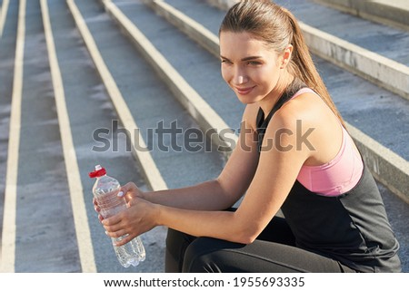 Young cute beautiful caucasian lady, wears long dark hair, is dressed in a black sports shirt and leggings, holds a bottle of water in her hand, sits on the steps after doing sports, enjoys rest. Stock photo ©