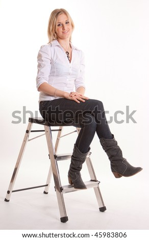 Young cute blond girl sitting on a stepladder