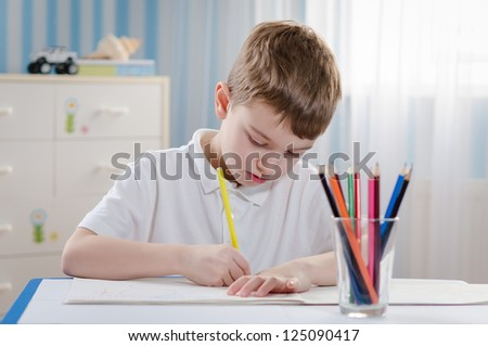 Young cute boy draws with color pencils in the children's room
