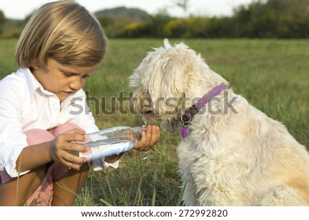 Young cute boy giving water to his dog, whilst playing on the grass